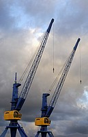 Two inoperative cranes looming into a cloud-covered evening sky