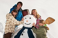 Austria, Salzburger Land, Altenmarkt, Family standing by snowman, smiling, portrait