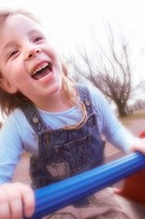 6 year girl laughing and playing on seesaw in childrens playground