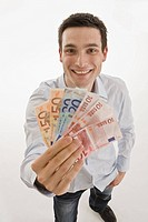 Businessman holding Euro notes, smiling, portrait