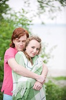 Germany, Bavaria, Ammersee, Young couple, woman wrapped in blanket, portrait