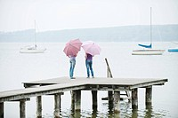 Germany, Bavaria, Ammersee, Two Women standing on jetty, holding umbrellas, rear view
