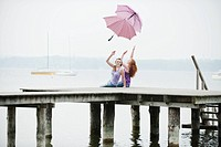 Germany, Bavaria, Ammersee, Women on jetty throwing umbrellas in air, portrait