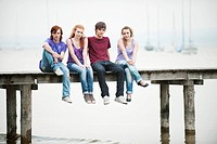 Germany, Bavaria, Ammersee, Four friends sitting on jetty