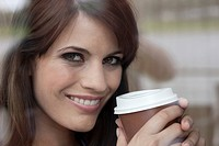 Germany, Cologne, Young woman holding plastic cup of coffee, smiling, portrait