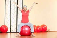 Senior woman sitting on gymnastic ball, smiling, portrait (thumbnail)