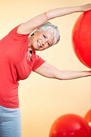 Senior woman practicing with gymnastic ball