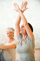 Woman in gym stretching arms, senior woman in background