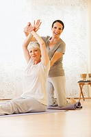 Two women doing exercise on mat, portrait