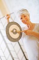 Senior woman holding gong, portrait