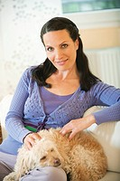 Woman sitting on a sofa with dog on her lap