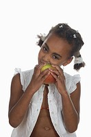 African girl 6-7 biting into apple, portrait (thumbnail)