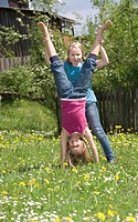 Austria, Salzkammergut, Two girls 10_11 in garden, girl helping friend to do handstand
