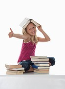 Portrait of a girl 10_11 with stacked books, thumbs up