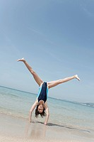 Spain, Mallorca, Girl 10_11 doing handstand on beach