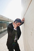 Spain, Mallorca, Businessman using mobile phone, leaning against wall