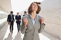 Spain, Mallorca, Business people walking together, Businesswoman in foreground cheering