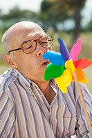 Spain, Mallorca, Senior man blowing toy wind wheel, portrait, close_up