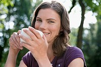 Germany, Hamburg, Woman holding cup of coffee, portrait, close_up