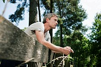 Germany, Hamburg, Man leaning against wooden fence