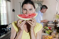 Germany, Hamburg, Couple in kitchen, woman holding melon slice