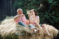 Germany, Bavaria, Couple sitting on haystack, having fun, portrait