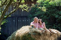 Germany, Bavaria, Couple sitting on haystack, smiling, portrait