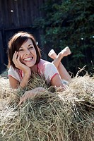 Germany, Bavaria, Woman lying on haystack, smiling, portrait