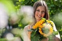 Germany, Bavaria, Woman holding bunch of sunflowers, smiling, portrait
