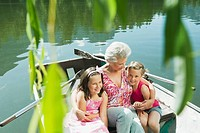 Italy, South Tyrol, Grandmother and grandchildren 6_7 8_9 sitting in rowing boat, portrait