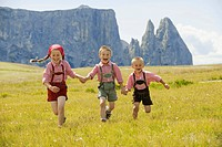 Italy, Seiseralm, Three children 4-5, 6-7, 8-9 running in field (thumbnail)
