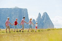 Italy, Seiseralm, Family walking in field