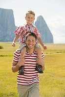Italy, Seiseralm, Fahter carrying son 6_7 on his shoulder, smiling, portrait