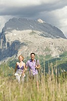 Italy, Seiseralm, Couple walking hand in hand in meadow