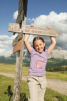 Italy, Seiseralm, Girl 6_7 standing by sign post, smiling, portrait