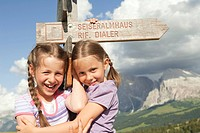 Italy, Seiseralm, Girls 6_7, 8_9 standing by sign post, smiling, portrait, close_up