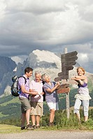 Italy, Seiseralm, Four persons standing next sign post