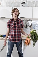 Germany, Berlin, Young man in kitchen holding bunch of carrots and knife, laughing, portrait (thumbnail)