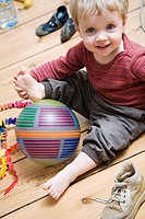 Germany, Berlin, Boy 2_3 sitting on wooden floor, playing with his ball, smiling, portrait, elevated view