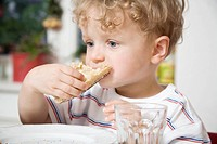 Germany, Berlin, boy 3_4 eating bread roll, portrait
