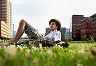 Germany, Berlin, Man relaxing on lawn, in background high rise buildings