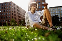 Germany, Berlin, Young man relaxing on lawn, in background high rise buildings