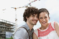 Germany, Berlin, Young couple in front of new building, cranes in background