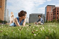 Germany, Berlin, Young woman lying in meadow holding mobile phone, man in background