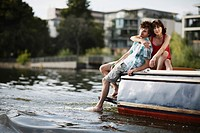 Germany, Berlin, Young couple sitting on motor boat, portrait