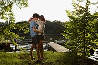 Germany, Berlin, Young Couple embracing by River Spree, view