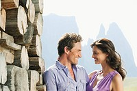 Italy, South Tyrol, Seiseralm, Couple standing in front of wood pile, portrait