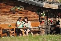 Italy, South Tyrol, Couple in front of log cabin drinking wine, portrait