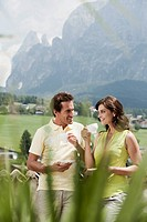 Italy, South Tyrol, Seiseralm, Couple holding coffee cup, outdoors