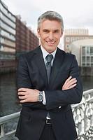 Germany, Hamburg, Businessman arms crossed smiling, portrait, close_up